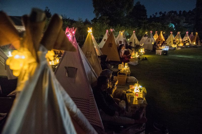 People watch movies from tents placed for social distancing at the campsites in Bandung