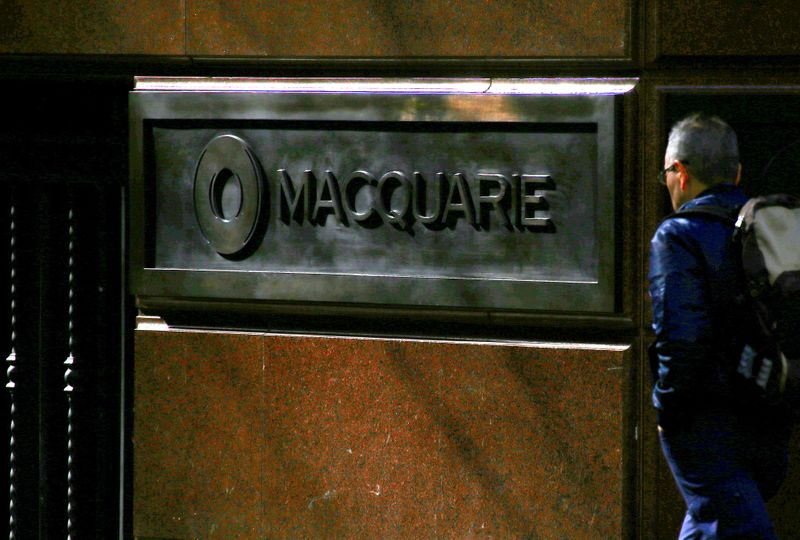 FILE PHOTO: A pedestrian walks past the logo of Australia's Macquarie Group at the firm's headquarters in central Sydney