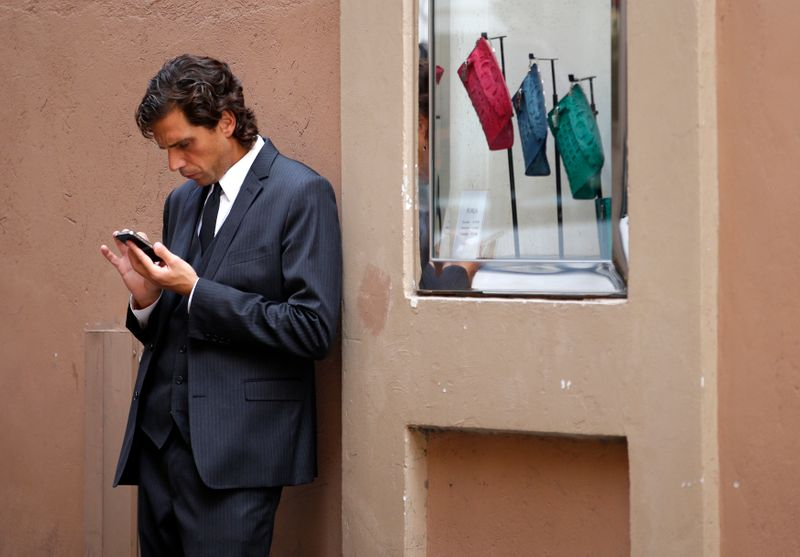 Man looks at his iPhone in Rome