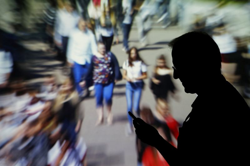 FILE PHOTO: A man looks at data on his mobile as background with crowd of people walking is projected in this picture illustration
