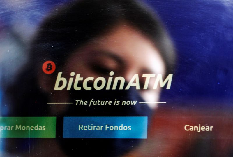 FILE PHOTO: An employee is reflected as she cleans the screen of a Bitcoin ATM in a shop in Mexico City