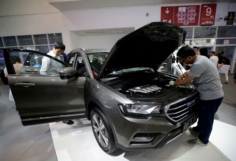 FILE PHOTO: Men check a Haval H6 from Great Wall Motors during the Auto China 2016 auto show in Beijing