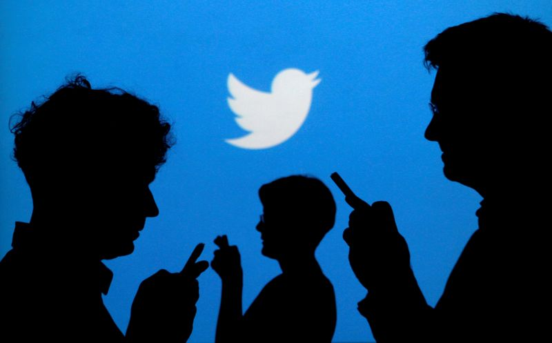 FILE PHOTO: FILE PHOTO: People holding mobile phones are silhouetted against a backdrop projected with the Twitter logo