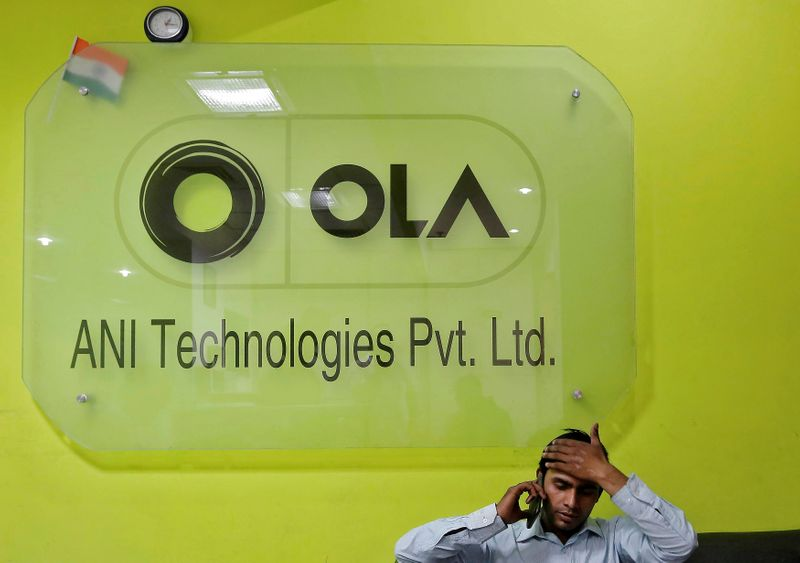 FILE PHOTO:  An employee speaks over his phone as he sits at the front desk inside the office of Ola cab service in Gurugram