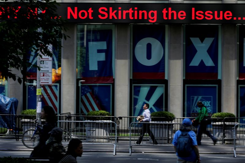 FILE PHOTO: People pass by ads of Fox News channel at the News Corporation building in New York City