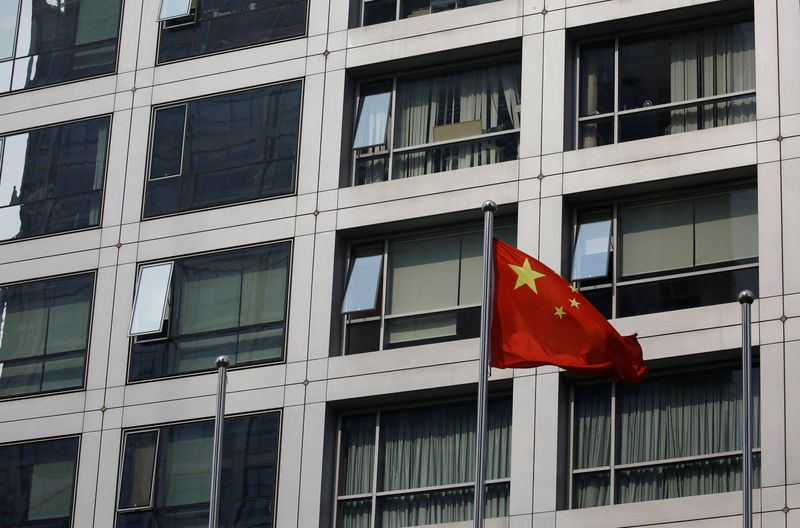FILE PHOTO:  Chinese national flag flutters near the building of China Securities Regulatory Commission (CSRC) at the Financial Street area in Beijing