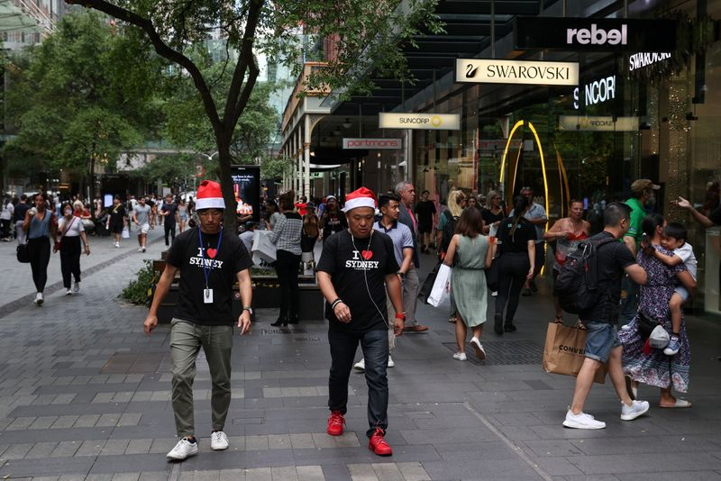 People wearing Santa hats walk through a shopping plaza decorated for the holidays in the city centre of Sydney
