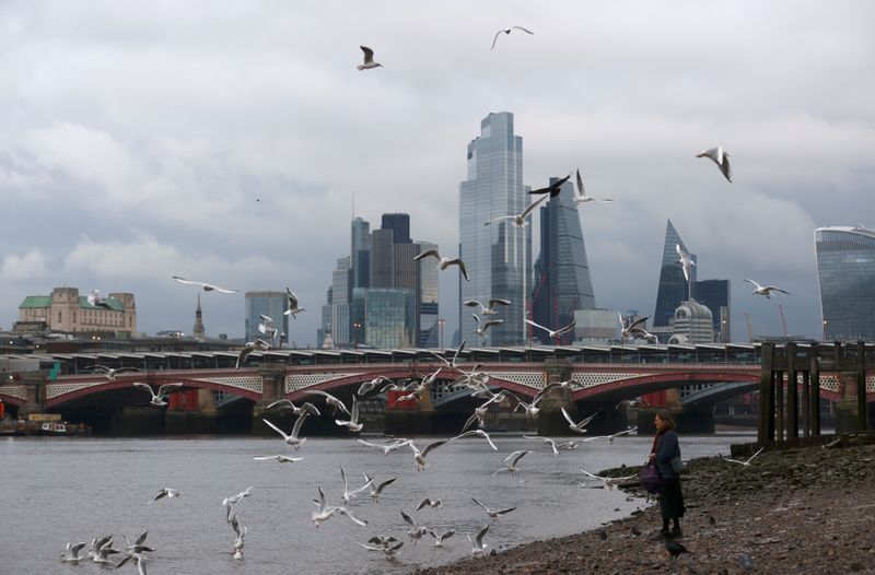 FILE PHOTO: A woman feeds birds on the bank of the river Thames with London's financial district seen in the background, amid the coronavirus disease (COVID-19) in London
