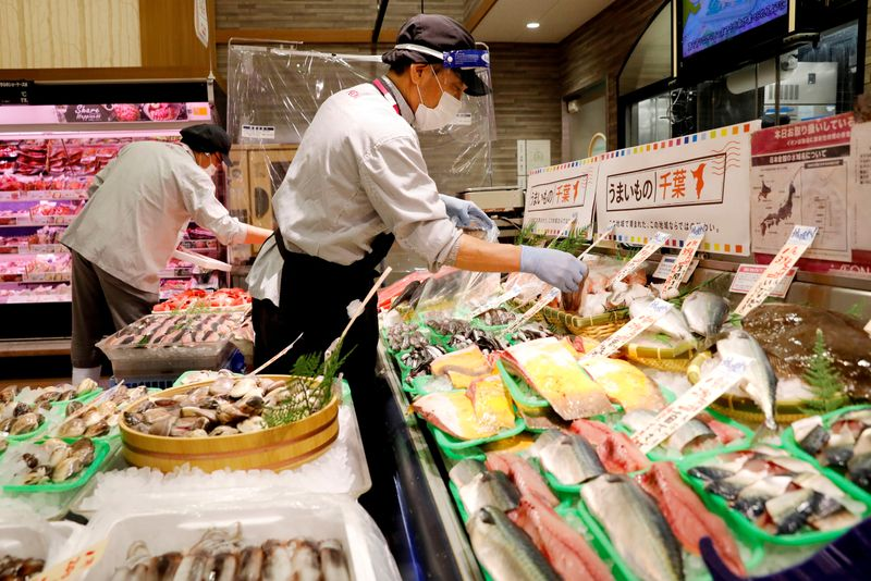 FILE PHOTO: A staff wearing a face shield sells fish at Japan's supermarket group Aeon's shopping mall as the mall reopens amid the coronavirus disease (COVID-19) outbreak in Chiba