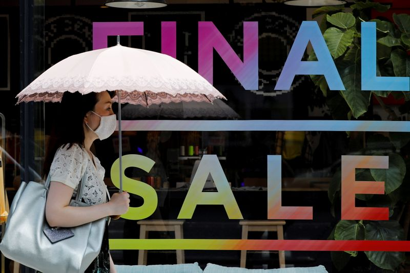 FILE PHOTO: A woman wearing a protective face mask walks past a sign for a sale at a shopping district in Tokyo