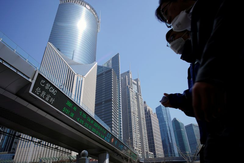 FILE PHOTO: Pedestrians wearing face masks walk near an overpass with an electronic board showing stock information in Shanghai