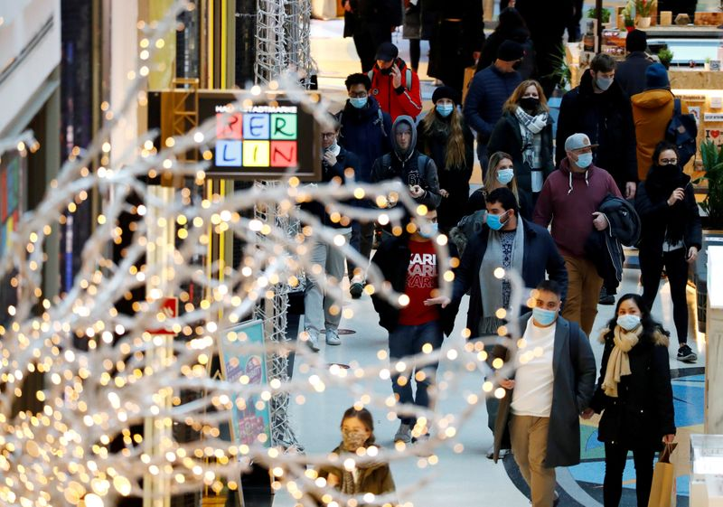 FILE PHOTO: People wear protective face masks as they walk beside Christmas decoration amid the coronavirus disease (COVID-19) outbreak in Berlin