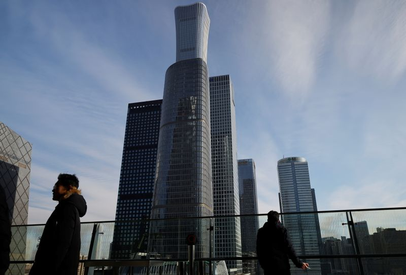 FILE PHOTO: Men stand on a balcony overlooking the central business district in Beijing
