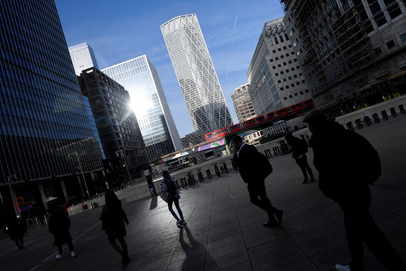 FILE PHOTO: People walk during the morning rush hour in the financial district of Canary Wharf amid the outbreak of the coronavirus disease (COVID-19) in London