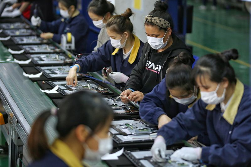 FILE PHOTO: Employees wearing masks work on a production line manufacturing display monitors at a TPV factory in Wuhan