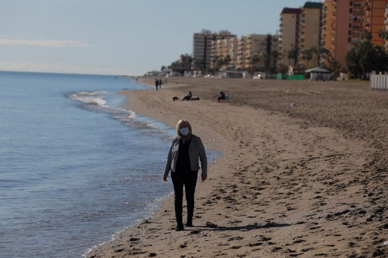 British resident Michelle Jones walks as she poses for a photo in front of the Mediterranean Sea on a beach in Fuengirola