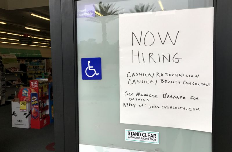 A handwritten hiring sign is posted outside a local drugstore in Solana Beach, California