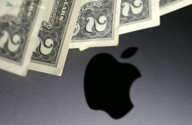 Photo illustration of U.S. dollar banknotes in front of the Apple logo