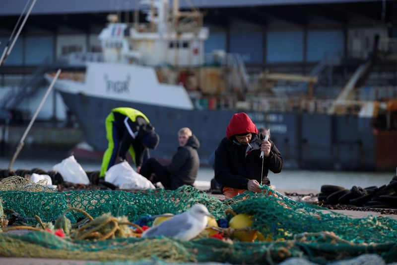 A fisherman repairs a fishing net on the dock of the port in Boulogne-sur-Mer