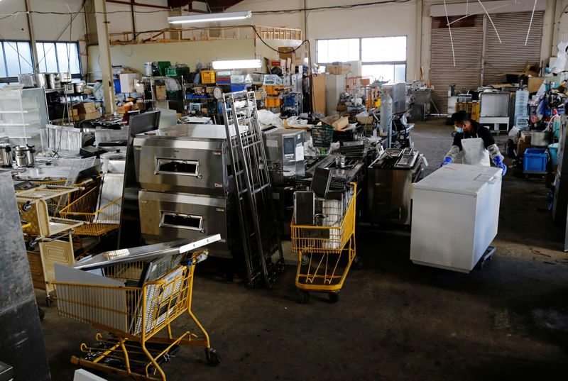 A worker carries a second-hand kitchen item at Tenpos Busters' reuse center in Yokohama