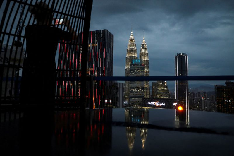 FILE PHOTO: A tourist takes a picture of the city skyline at a bar in Kuala Lumpur