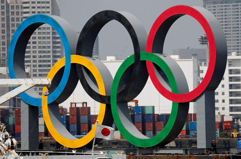 FILE PHOTO: The giant Olympic rings are seen behind Japan's national flag at the waterfront area at Odaiba Marine Park in Tokyo