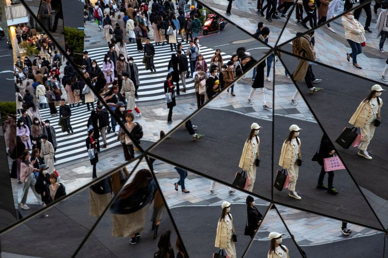 People wearing protective masks, following an outbreak of the coronavirus disease (COVID-19), are reflected in the mirror at a shopping mall in Tokyo
