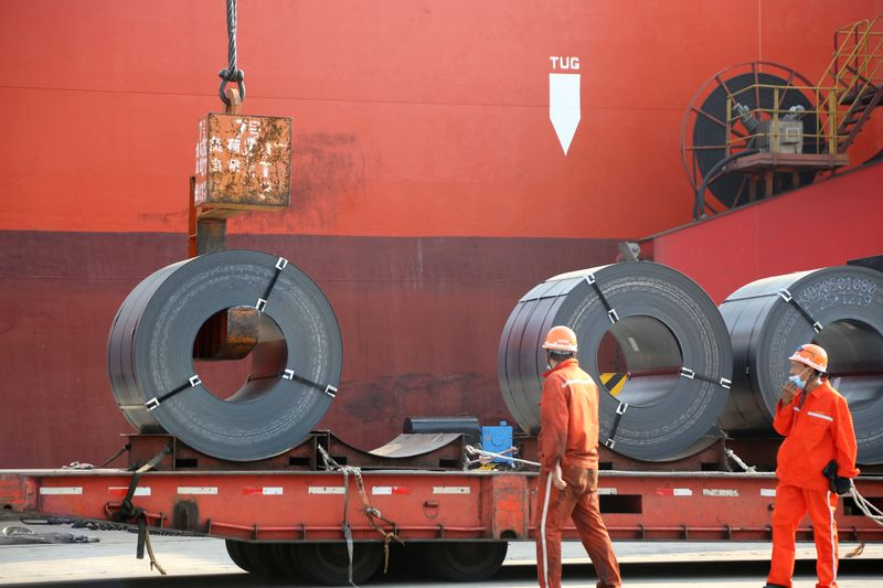 FILE PHOTO:  Workers load steel products for export to a cargo ship at a port in Lianyungang