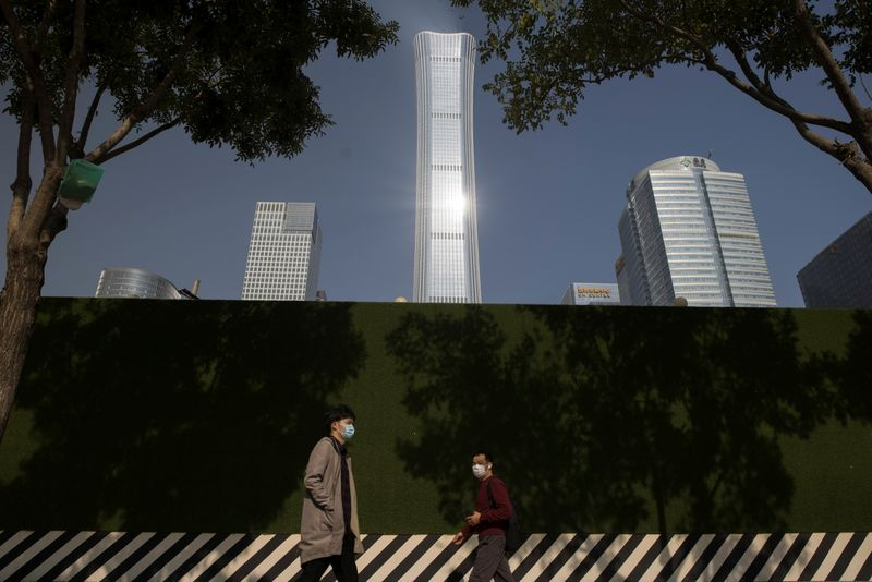 People walk past the skyline of the Central Business District (CBD) on the day that Chinese leaders elaborate on their 14th Five-Year plan in Beijing