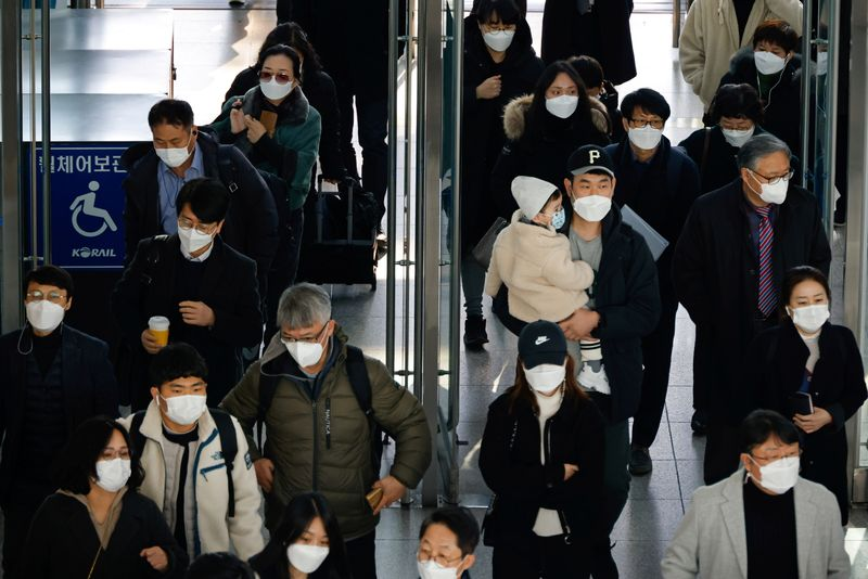 FILE PHOTO:  People wearing masks walk at a railway station amid the coronavirus disease (COVID-19) pandemic in Seoul