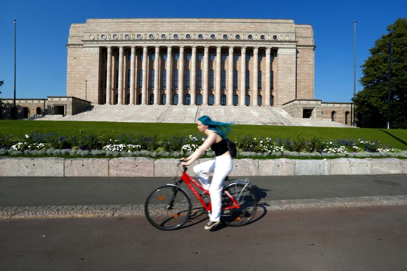 FILE PHOTO: A woman rides a bike past Finland's Parliament house in Helsinki