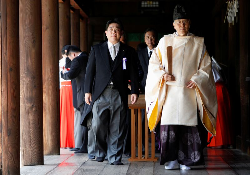 FILE PHOTO: Japan's Land, Infrastructure, Transport and Tourism Minister Hata and other lawmakers are led by a Shinto priest after offering prayers to war dead at Yasukuni Shrine in Tokyo