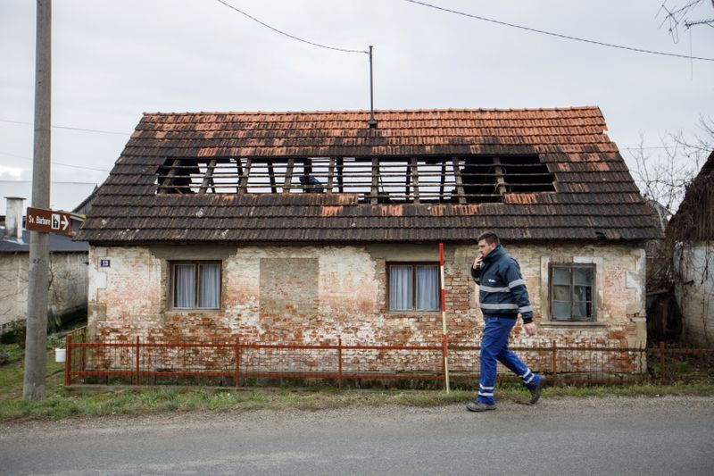 A man walks next to a damaged house after a 5.2 magnitude earthquake, in Brest Pokupski village