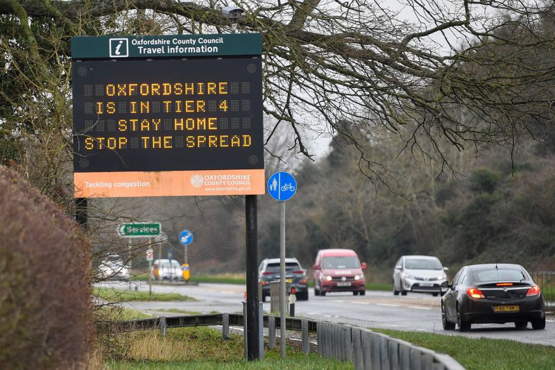 Vehicles drive past a roadside public health information sign, amidst the spread of the coronavirus disease (COVID-19) pandemic, near Oxford