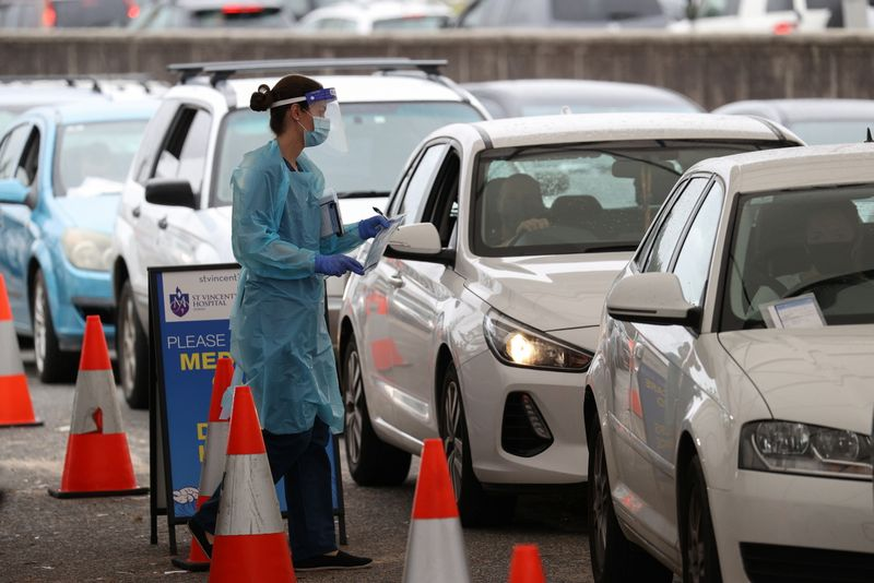FILE PHOTO:  Vehicles queue as medical personnel administer tests at a drive-through COVID-19 testing centre in Sydney