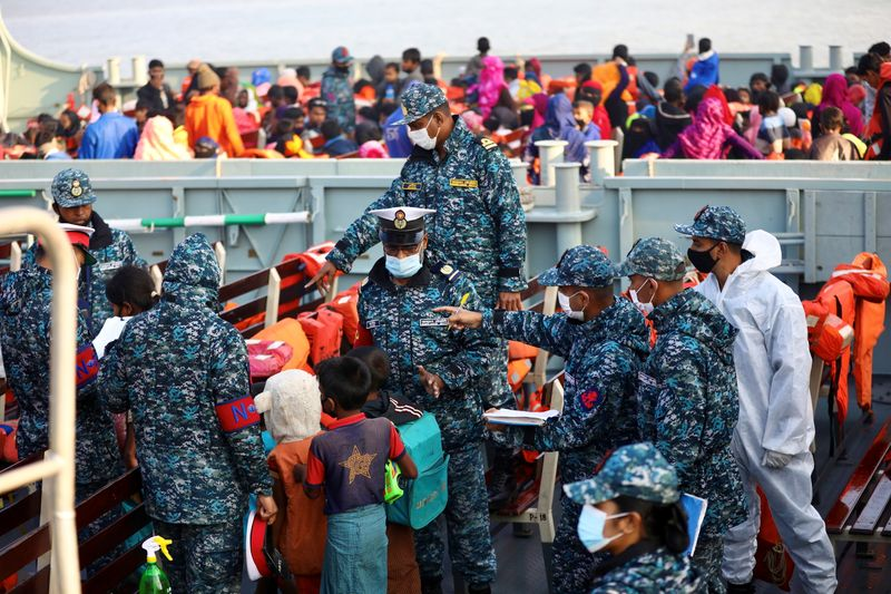 Bangladesh navy personnel check Rohingyas before they board a ship to move to Bhasan Char island in Chattogram, Bangladesh