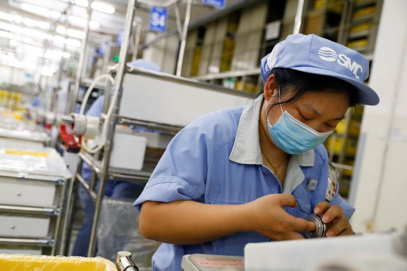 FILE PHOTO: An employee wearing a face mask works at a factory of the component maker SMC during a government organised tour of its facility following the outbreak of the coronavirus disease (COVID-19), in Beijing