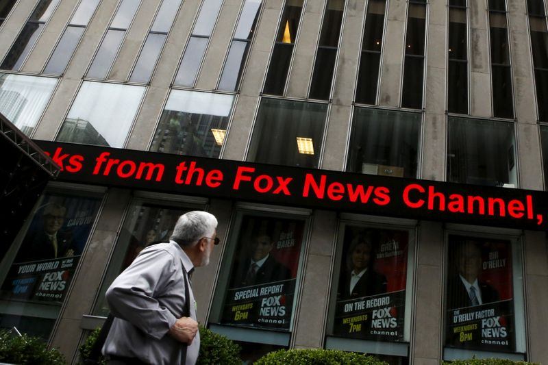 FILE PHOTO: A man reads a headline at the Twenty-First Century Fox Inc headquarters in the Manhattan borough in New York