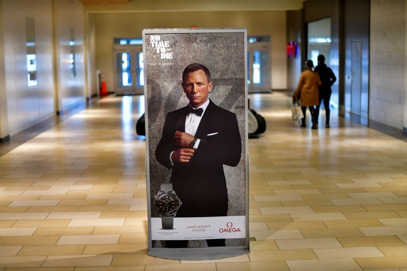 FILE PHOTO: Shoppers walk past an advertisement for the upcoming James Bond film