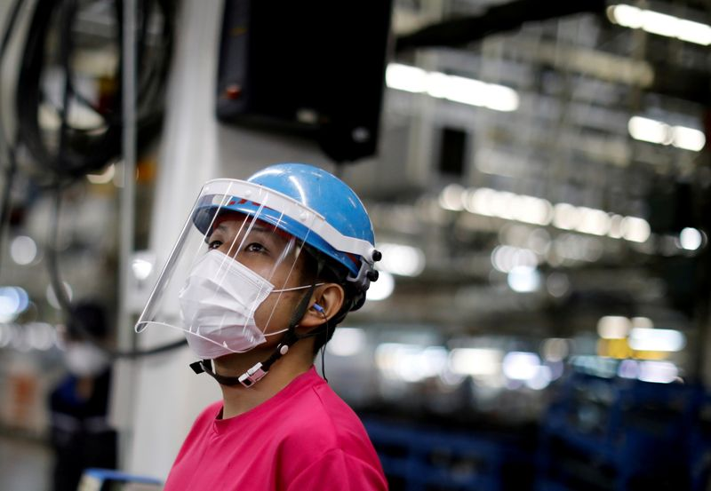 FILE PHOTO: FILE PHOTO: An employee wearing a protective face mask and face guard works on the automobile assembly line during the outbreak of the coronavirus disease (COVID-19) at the factory of Mitsubishi Fuso Truck and Bus Corp. in Kawasaki