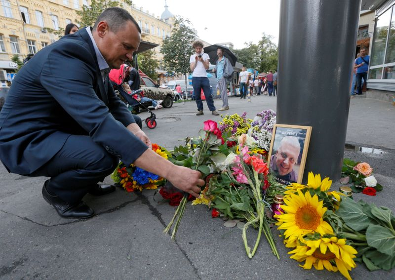 FILE PHOTO: Man places flowers at site where journalist Sheremet was killed by a car bomb in Kiev