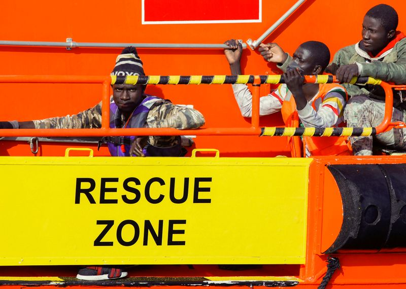 FILE PHOTO: Migrants wait to disembark from a Spanish coast guard vessel, in the port of Arguineguin