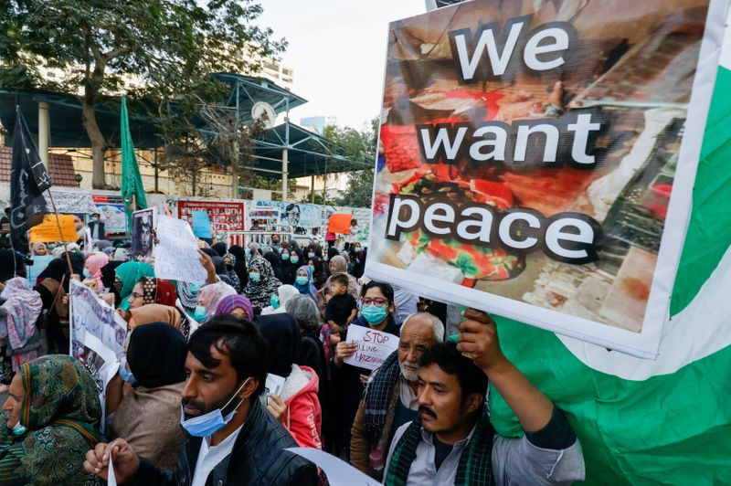 People carry placards demanding justice, during a protest in Karachi