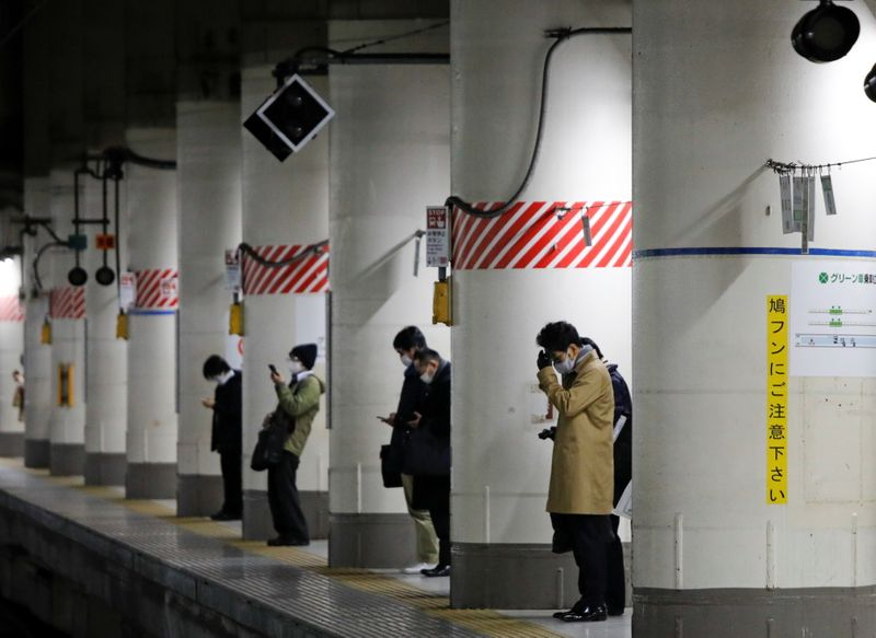 Commuters wearing protective face masks wait for arrival of a train on the way home, in Tokyo