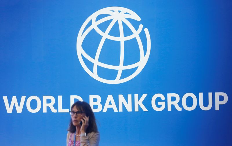 A participant stands near a logo of World Bank at the International Monetary Fund - World Bank Annual Meeting 2018 in Nusa Dua