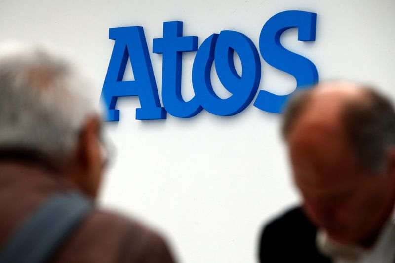 People walk in front of the Atos company's logo during a presentation of the new Bull sequana supercomputer in Paris