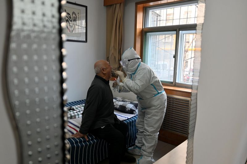 Medical worker in protective suit collects a swab from an elderly during a door-to-door nucleic acid sampling in Shijiazhuang