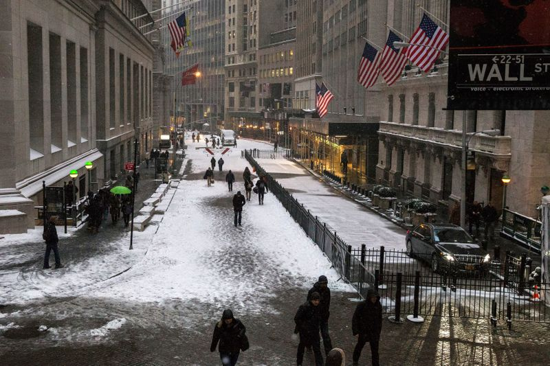 Commuters walk through the Financial District during a snow storm in Lower Manhattan