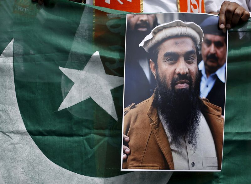 FILE PHOTO: A supporter of Shiv Sena holds Pakistan's national flag and a portrait of Lakhvi during a protest in New Delhi
