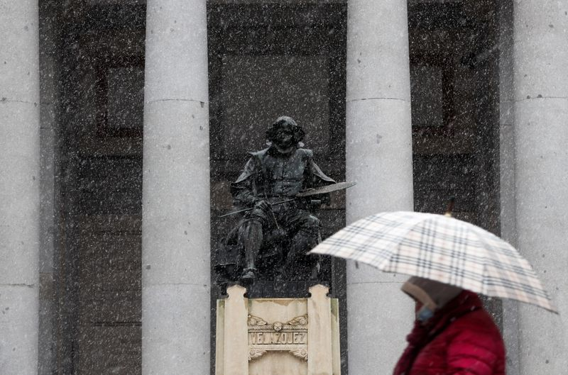 FILE PHOTO: Woman walks past a statue of Spanish painter Diego Velazquez outside the Prado Museum during a snowfall in Madrid